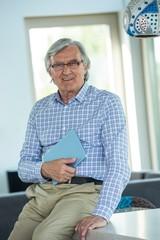 Retired man holding tablet