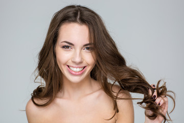 Smiling woman with fresh skin touching her hair