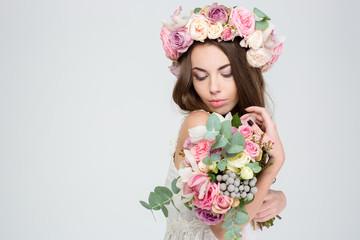 Romantic lovely woman in wreath of roses with flower bouquet