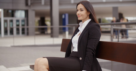 Optimistic young professional woman sitting alone on bench outside office building with pleasant grin