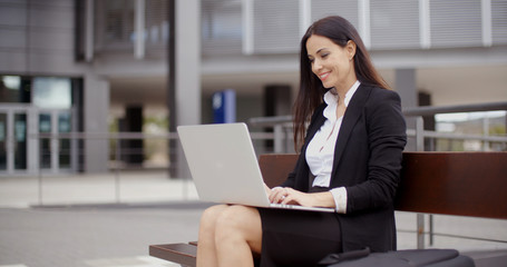 Cute business woman sitting alone on bench in front of office building working on laptop computer