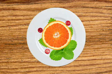 plate with orange slice, mint herb and berry on wooden table