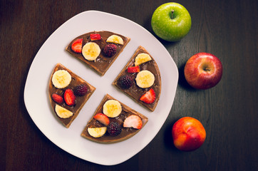 Pancake cut in four parts decorated with fruits, flanked by two apples and a peach