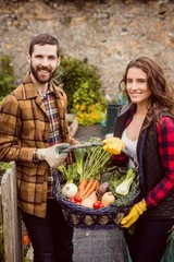Proud couple showing basket of vegetables