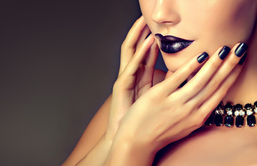 Beautiful girl showing black  manicure .  makeup and cosmetics