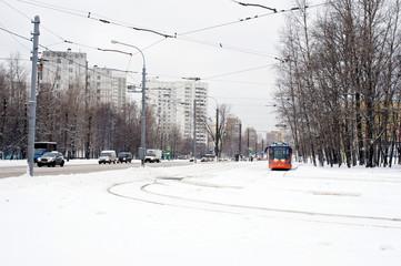 Orange tram and car road in winter