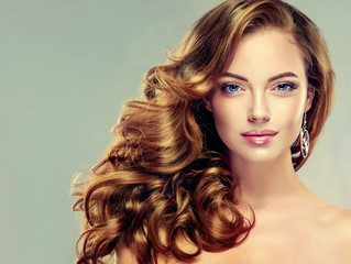 Beautiful girl with long wavy hair . Brunette with curly hairstyle . jewelry earrings  - fototapety na wymiar
