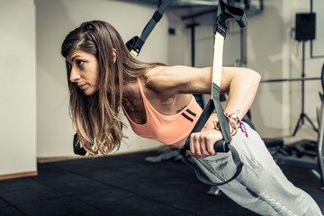 Woman training with elastics in the gym