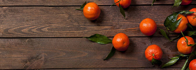 Photo of fresh mandarines on old brown wooden table