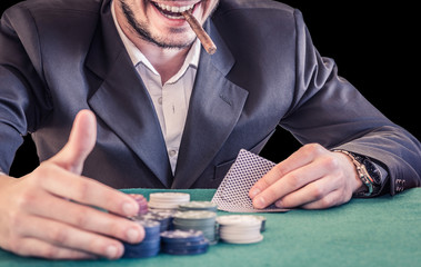 Man smiling and smoking a cigar while playing poker - caucasian people - lifestyle, people and poker concept
