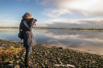 Female photographer shooting water reflection at sunset