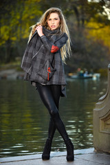 Stylish young woman posing against lake in the park at nice autumn day, wearing coat and leggings.