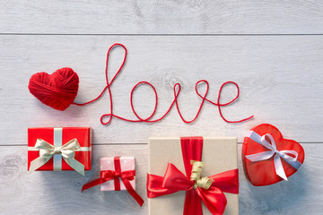 "Red heart, Word ""Love"" and Valentines Day gifts boxes on wooden background. Valentines Day background"