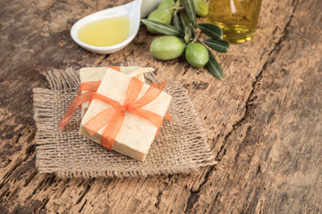 natural olive oil soap bars on wooden table decorated with olives and oil bottle