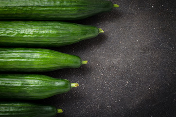 Frame of green cucumbers on dark background