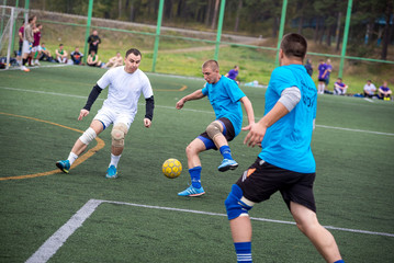 Men playing street soccer. Emotional moment. Three 3 players running after the ball. On the grass at the stadium. Two men in blue shirt, one in white. Against the backdrop of pine forest. Yellow ball
