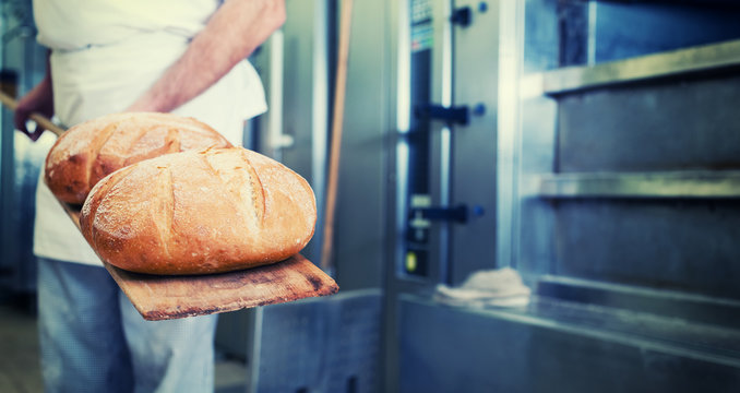 Bäcker mit Brot in Bäckerei auf Schaufel steht vor dem Backofen