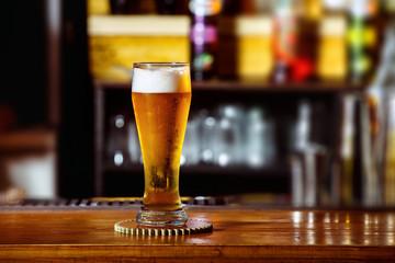 Closeup image of glass with golden unbottled light beer at bar