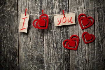 Handwritten words I love you and hearts on wooden background.