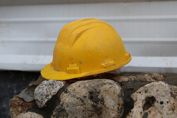 Work Helmet. Work helmet of a construction worker on a rock fence in the construction site. Wet safety helmet of a construction worker in front of a corrugated iron fence in a rainy day.