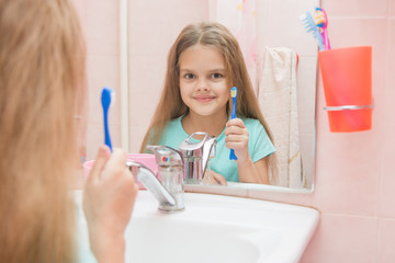 Six year old girl opening her mouth treats teeth in reflection in a mirror, while in the bathroom