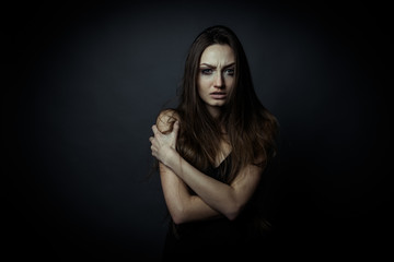 Portrait of a sad woman with crossed hands