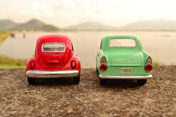 Red and green toy car park couple on the road
