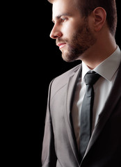 Thoughtful young bearded man in suit and tie