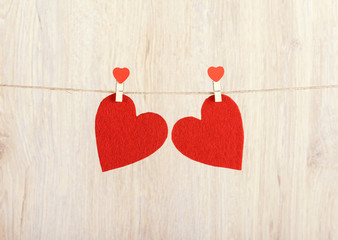 Two red hearts hung on the rope