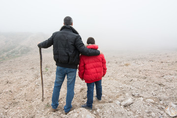 Concept of family escaping.  Father and son in a mountain road w