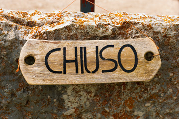 Chiuso - Closed Sign in Italian Language / Wooden rustic sign with text Chiuso (closed in italian language). Hanging with a rope on a rock