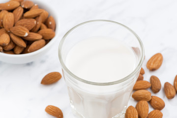 almond milk in a glass on white table, top view, selective focus