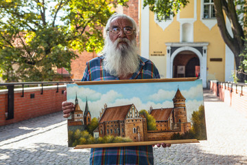 Portrait of handsome elderly aged man with magnificent gray-haired beard and his picture of castle behind him.