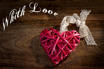 red wooden heart with lace bow on wood and with love written