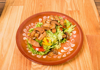 Warm pork salad with mushrooms.