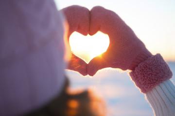 Woman hands in winter gloves Heart symbol