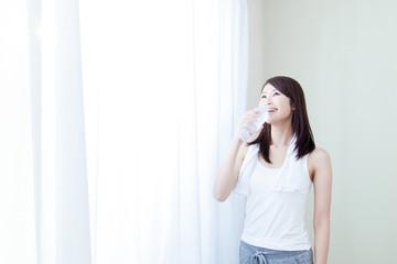 女性 タンクトップ 朝 朝日 カーテン 水 ペットボトル 飲む 飲料水
