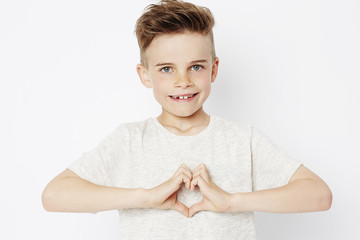 Boy gesturing love with hands, portrait