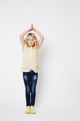 Young kid in yoga pose against white background