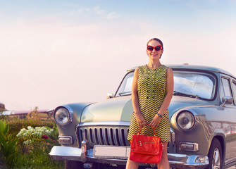 Brunette woman standing near retro car