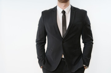 part of business man body in black suit with hands in pockets on