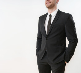part of smiling business man in black suit with hands in pockets