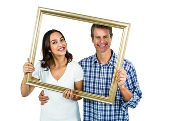 Happy couple looking through picture frame
