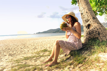 Young woman drinking coconut cocktail on tropical beach