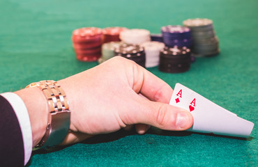 Close up of a pair of aces in a hand during a poker game - poker and lifestyle concept