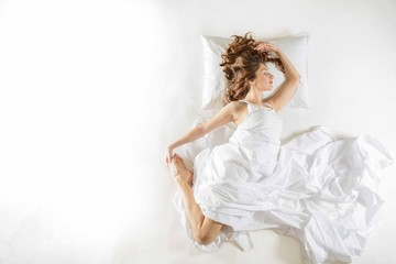 Expressive woman sleeping. Full length high angle view of a young woman sleeping on white background. Expressive woman in action, dreaming concept. Ballet dancer rehearsing in her sleep