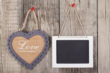 Empty wooden blackboard sign and heart shape frame.