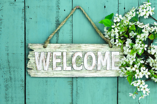 Welcome sign with flowers hanging on wood door