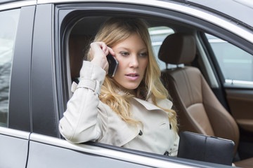 Young woman sitting in a car chatting on a mobile