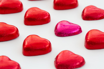 Heart shaped, Valentine chocolates on an isolated white background. Candy in rows in a grid pattern and with an odd chocolate in one row.